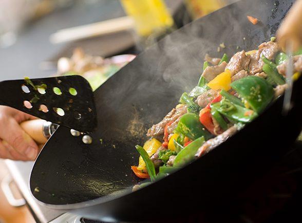 lähikuva wokkipannusta, jossa kokataan vihanneksia
