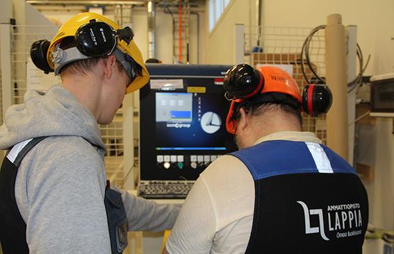 opiskelijoita ohjelmoimassa konetta
