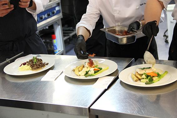 okokkiopiskelijat kokoavat lautaselle annoksia keittiössä