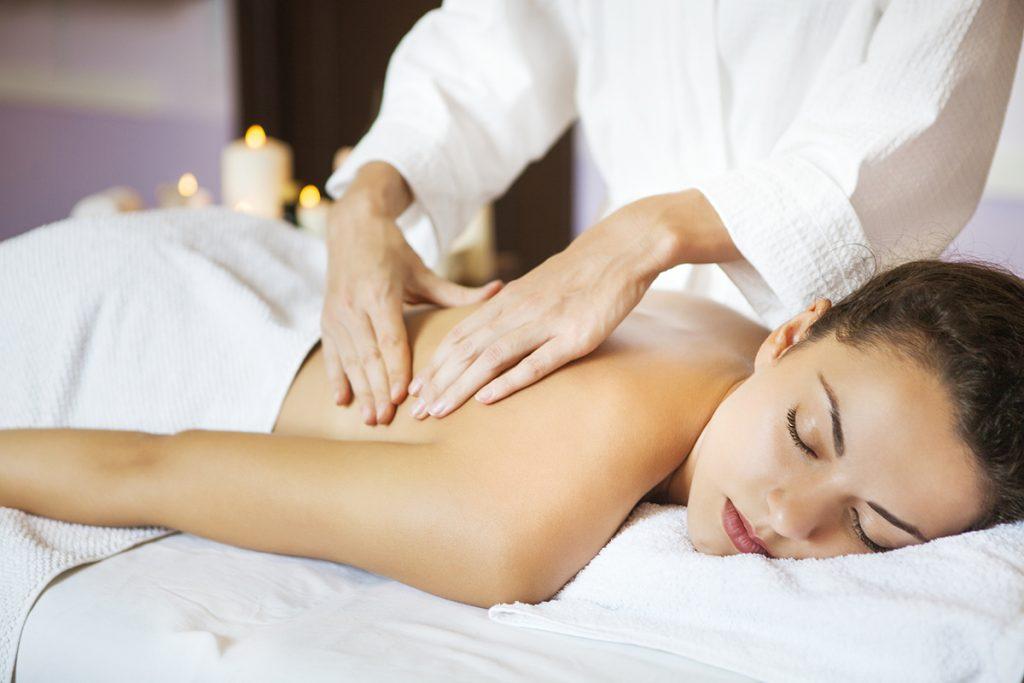 nainen makaa hierontapöydällä ja hieroja hieroo selkää