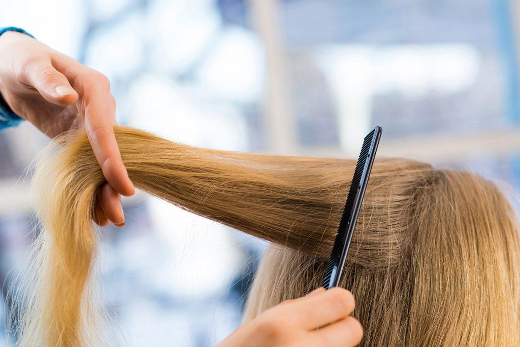 lähikuva pitkistä hiuksista, joita kampaaja kampaa