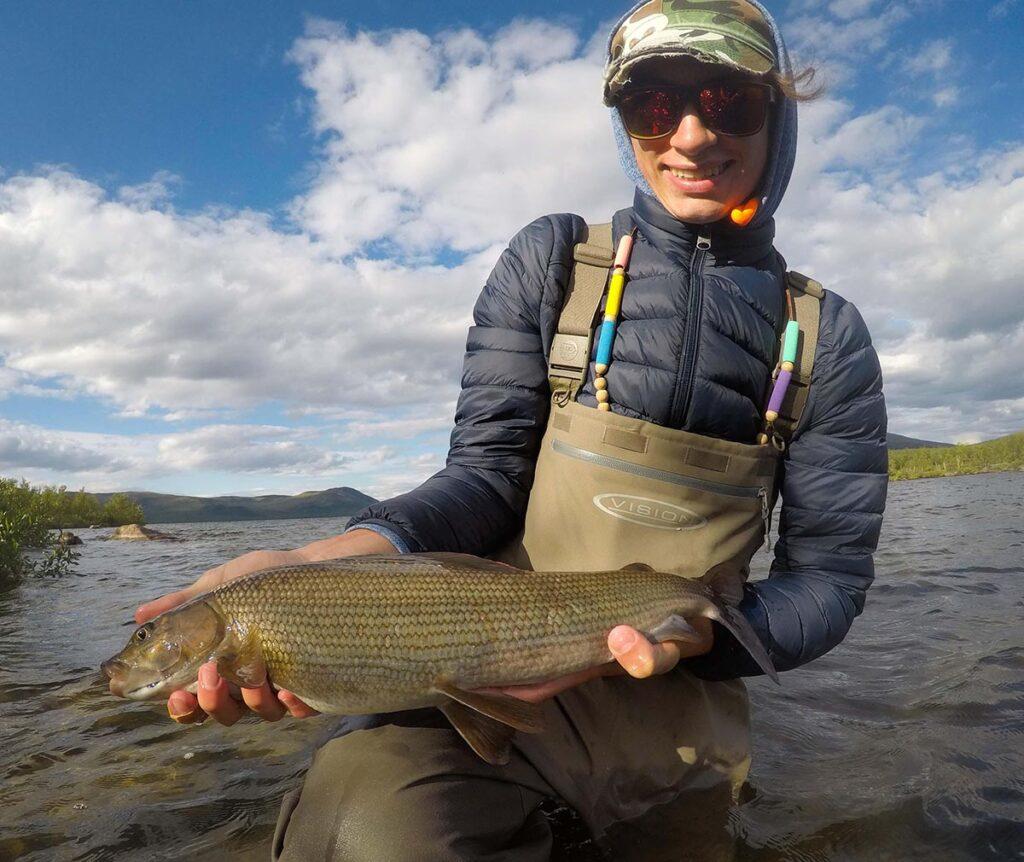 onnellinen kalastaja pitää kalaa kädessään